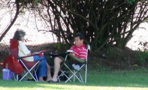 A couple sits in the shade reading at Wilderness Park in Downey, Calif. Wilderness Park is one of the most popular parks in the city. It includes several lakes where wildlife have claimed its home. Photo by: Alicia Edquist